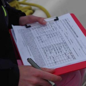 Recording marine mammal survey data during research trip.
